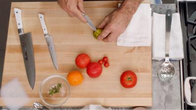 Thomas Keller cutting tomatoes on cutting board
