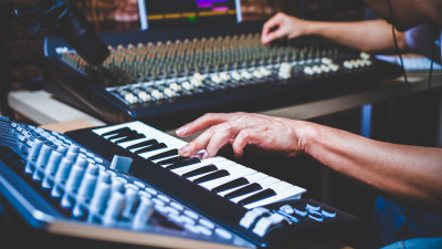 Person playing piano with synthesizers in studio