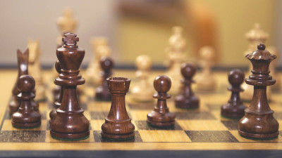 Wooden chess pieces on wood board