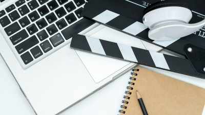 Movie clapperboard with notebook and laptop computer