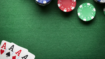 Playing cards on green table with poker chips