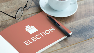 Booklet with election written on it on desk with coffee and glasses