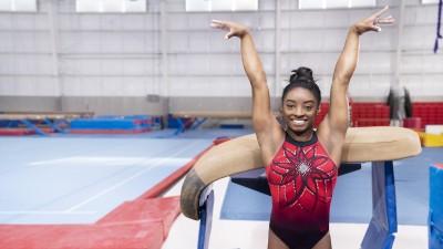 Simone Biles standing in front of gymnastic vault