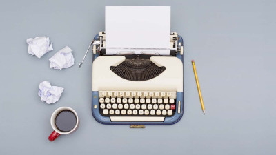 Vintage typewriter with coffee and crumpled pieces of paper