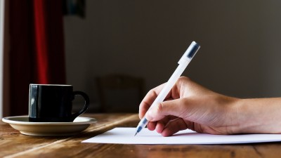 Person writing with pen and coffee on wood desk