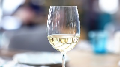 a glass of wine on a table on a bright day