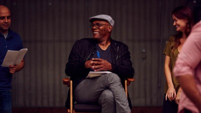 Samuel L. Jackson sitting in chair on set with actors