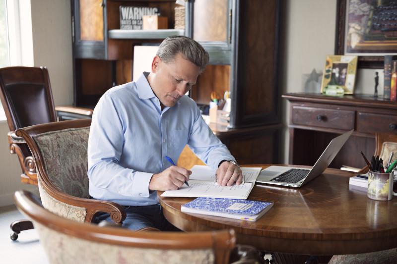 David Baldacci writing at desk