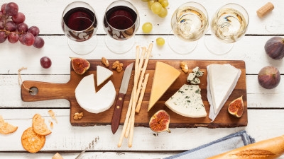 Wine and charcuterie board on white wood