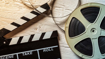 Film clapperboard with film on white wood