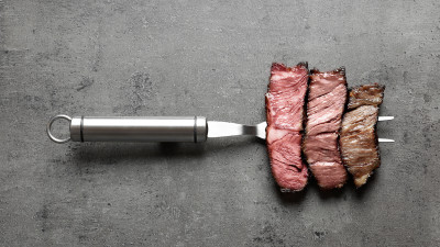 medium rare, well done, and rare steak on a grilling fork
