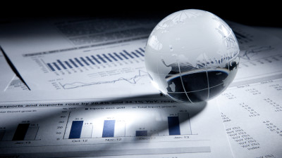 Glass globe on business graph pieces of paper