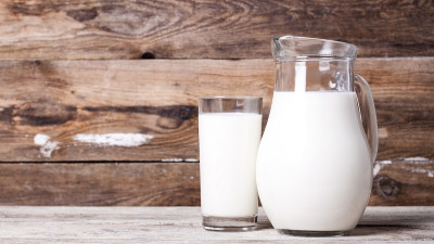 Glass of milk and pitcher of milk on wood background