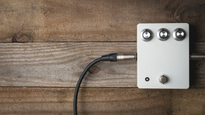 Silver guitar pedal on wood