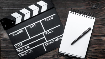 movie clapperboard with notepad and pen