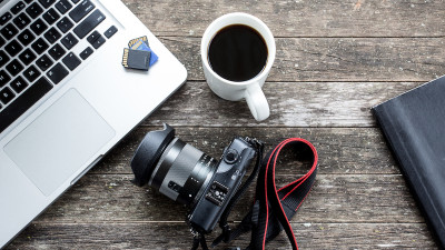 laptop with coffee, DSLR camera, and coffee