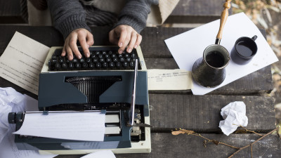 Woman typing on typewriter on park picnic table