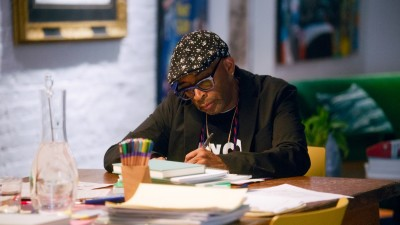 Spike Lee writing on paper at desk