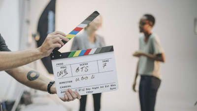 Actors standing behind a movie clapperboard on set