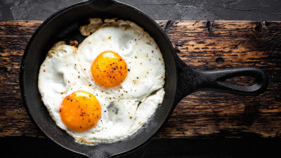 Fried eggs in cast iron skillet on wood