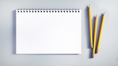 notepad with pencils on white background