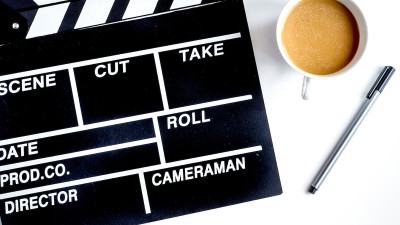 Movie clapperboard with coffee and pen on white background