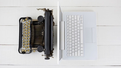 laptop and typewriter on white wood