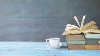 Stack of books with book open and coffee cup on blue wood