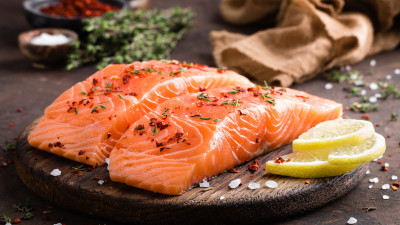 Raw salmon with spices and lemon on wood plank
