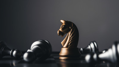 Gold chess piece on board with gray pieces