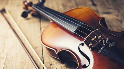Violin with violin bow on wood floor