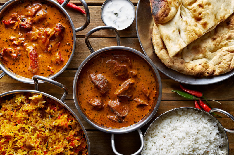 Indian dishes in bowls with naan and rice