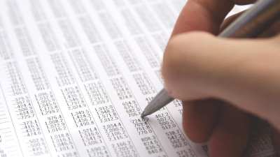 Person circling numbers on paper with pen
