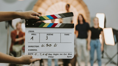 Actors standing behind someone holding a movie clapper board