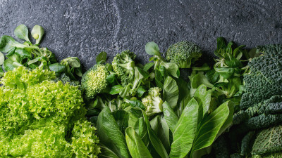 Various cooking greens on gray slate background
