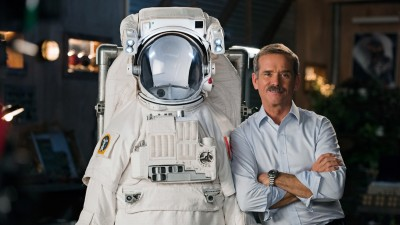 Chris Hadfield standing next to astronaut suit