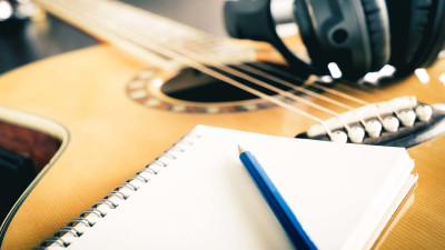 Guitar with notebook and headphones