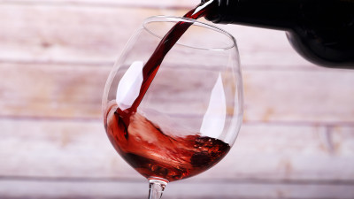 Red wine being poured into a wine glass with wood background