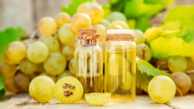 Grapeseed oil in glass containers with grapes on wood