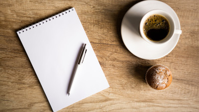 Blank notebook with pen and coffee with muffin