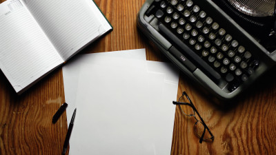 Typewriter with notebook, paper, pen, and glasses