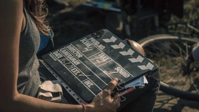 Women holding movie clapperboard on set outside