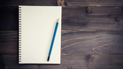 Blank notebook with blue pencil on dark wood