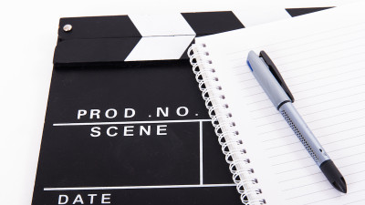 Movie clapperboard with notebook and pen