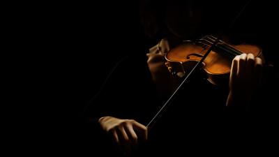 women playing violin with dark black background