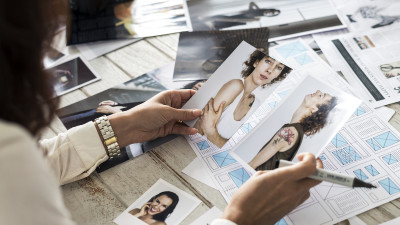 Woman picking model photos on desk