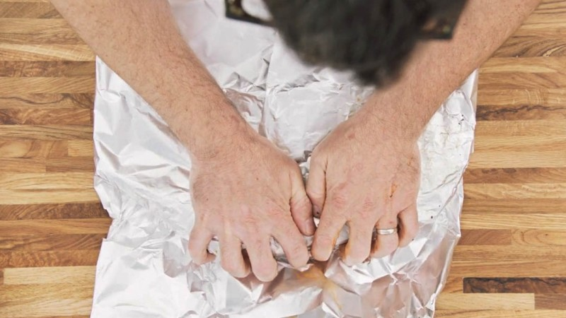 Aaron Franklin wrapping ribs with tinfoil step 2