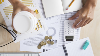 Person working at desk with coffee, business items and calculator