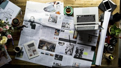 Newspaper spread on table with laptop and coffee