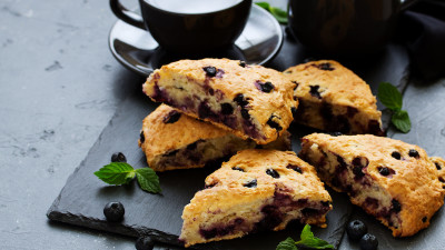Blueberry scones on black slate with coffee